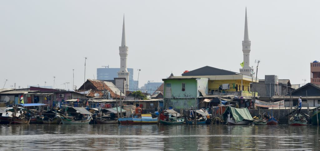 "Remnants of a shanty town near to Sunda Kelapa Harbor - those are being torn down & replaced by concrete nightmare towers. Long term vision is a nightmarish replica of Singapore. ""Progress."" Minarets of a mosque are also visible (June 2016)."